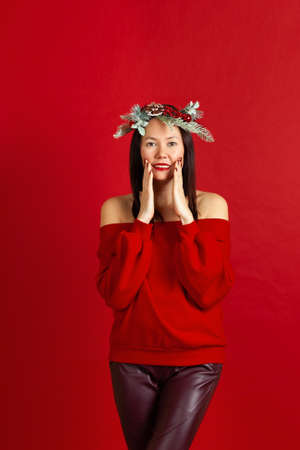 full-length portrait of a smiling Asian young woman with a Christmas wreath, red lipstick and hands on her face