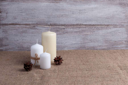 mock up of two white candles in jute rope and vanilla candle, cones on a wooden background and burlap Stock fotó