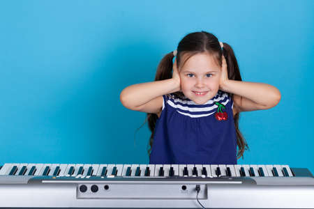 mock-up portrait of a smiling girl who covers her ears with her hands to avoid hearing anything, electronic synthesizer