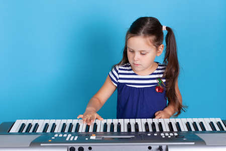 front view close up portrait of a girl enthusiastically playing n piano isolated on light blue background