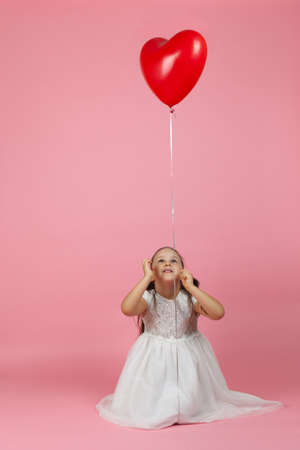 A mischievous, playful child with ponytails and a white dress sits on the floor and looks at a red heart-shaped balloon above her , isolated on a pink background
