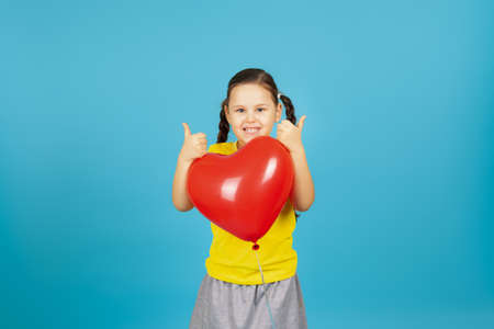 close-up cheery, gladsome pigtailed girl in a yellow T-shirt hugs a red heart-shaped balloon and gives a thumbs up isolated on a blue background
