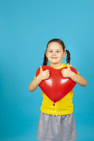 Close-up a smiling, contented pigtailed girl in a yellow T-shirt hugs a red heart-shaped balloon and gives a thumbs up isolated on a blue background
