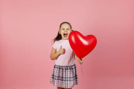 close-up enthusiastic ecstatic rapturous girl in pink dress holds red balloon in the shape of heart and gives thumbs up isolated on a pink background