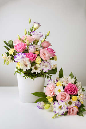 mock up two bouquets of different sizes of roses, daisies, lisianthus, chrysanthemums, unopened buds in a white paper box on a white background, one bouquet is on the table