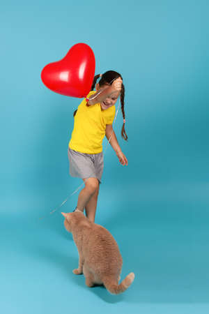 a full-length girl with pigtails in a yellow T-shirt and a gray skirt plays with a cat with a string from a red balloon in the form of a heart , isolated on a blue background