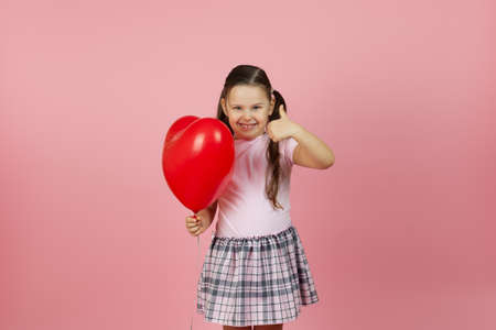 portrait of cheery, gladsome child in a pink dress holding a red balloon in the shape of a heart and giving a thumbs up isolated on a pink background