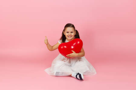 attractive, gorgeous girl in white dress holding red heart shaped balloon and sitting on the floor and giving thumbs up isolated on a pink background