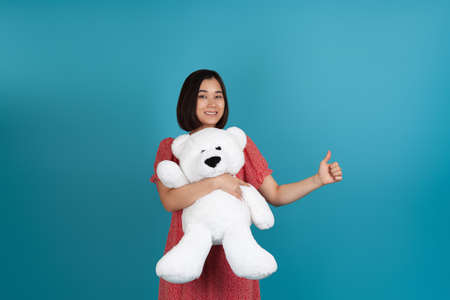 close up portrait of a smiling happy young Asian woman in a red dress hugging a white Teddy bear and giving a thumbs up isolated on a blue background