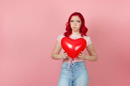 a resentful, moody woman with red hair and jeans holds a flying red balloon in her hands and inflates her cheeks, isolated on a pink background Banco de Imagens