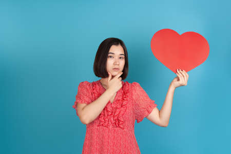 close-up thinking, decision-making young Asian woman in a red dress holds a large red paper heart in her hands and touches her chin with her hand , isolated on a blue background Banque d'images