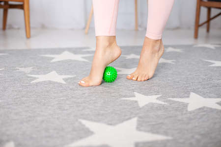 close-up two feet with a pedicure of a young woman, one foot stands on a green spiki massage ball on a gray carpet with white stars in the home interior