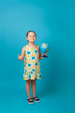 positive, joyful girl in a white summer dress with colorful circles holding a globe in her hand and giving a thumbs up, isolated on a blue background
