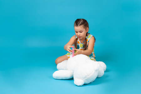 positive girl sitting on the floor gives an injection or vaccination with a toy syringe in the of a white teddy bear isolated on a blue background