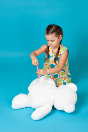 girl sitting on the floor gives an injection or vaccination with a toy syringe in the of a white teddy bear isolated on a blue background