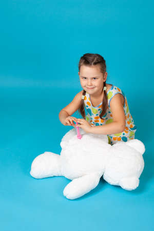 girl sitting on the floor makes an injection or vaccination with a toy syringe in the of a white teddy bear isolated on a blue background