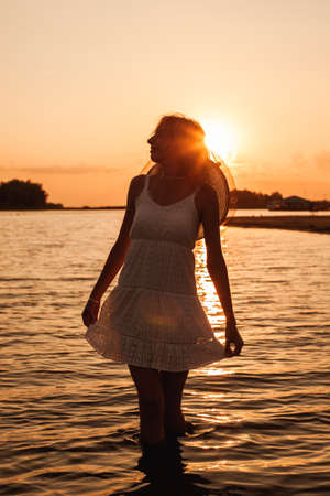 A young woman on the background of the sunset. Photo of a beautiful blonde holding the hem of a white summer dress and wearing a straw hat, posing in the water and admiring nature Archivio Fotografico