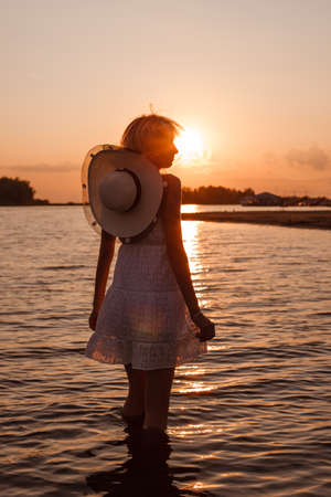 A young woman on the background of the sunset. A profile picture of a beautiful blonde in a white dress and a straw hat with a ribbon around her neck standing in the water
