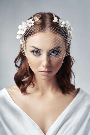 Portrait of a bride with birdcage veil.