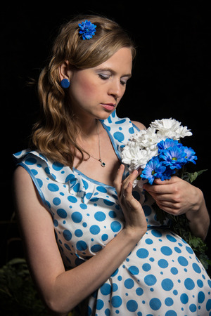 feminity: woman with a bouquet of flowers in a white dress with blue patches