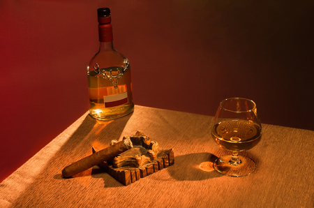 drunks: Whiskey with lit a cigar and pour into a glass of whiskey over brown background