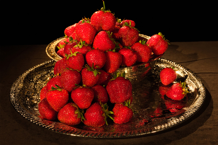 chromed: Strawberries berry on a black background with water drops in chromed metal bowl