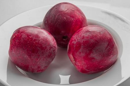 plato del buen comer: Tres manzanas rojas en un plato blanco de cerca
