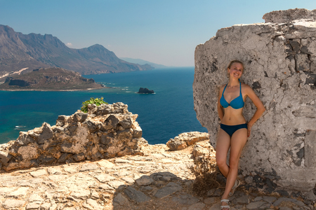 girl in a blue bathing suit hiding from the sun behind a boulder on top of beautiful marine species. In the Mediterranean Sea