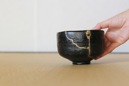 Serving a repair of crack pottery tea cup  horizontal