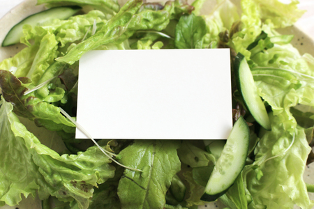 Fresh green salad on white wooden table a blank card