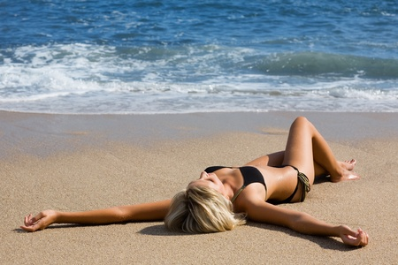 Attractive girl lying on the sand by the sea. Sunny day.
