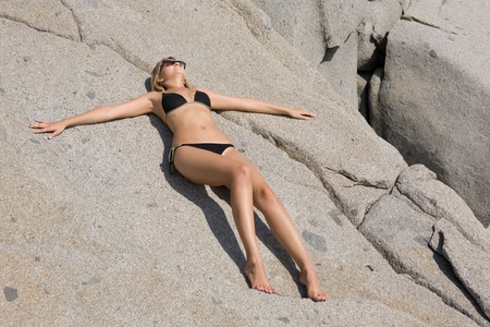 Attractive girl relaxing on a beautiful rocky beach by the sea. photo