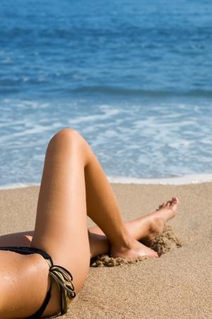 Sexy girl in a bikini lying on a beach. Stock Photo - 9749307