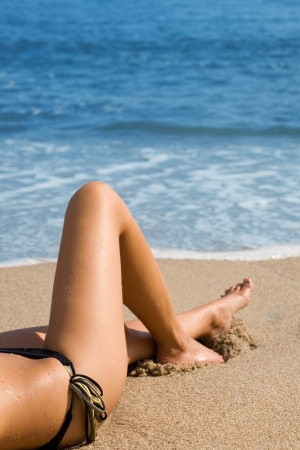 Sexy girl in a bikini lying on a beach. photo
