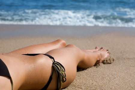 Lower half of the girl body lying on the beach by the sea. Stock Photo