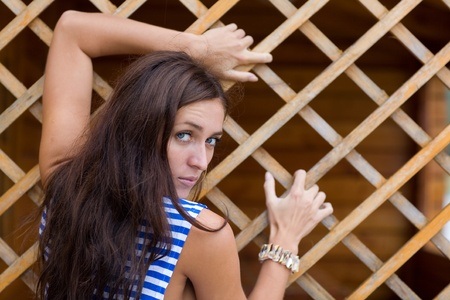Brunette in striped shirt with a lattice of wood. photo