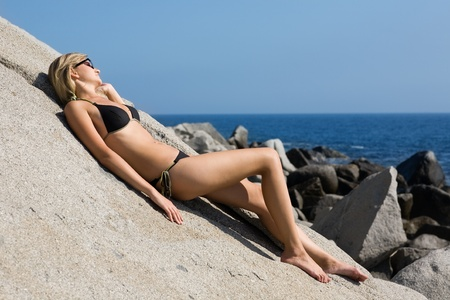 Attractive girl relaxing on a beautiful rocky sea beach. photo