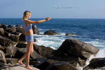 Attractive girl relaxing on rocky beach by the sea. In the sky flying ducks. photo