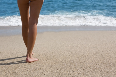 Young woman with shapely legs against the sea. photo