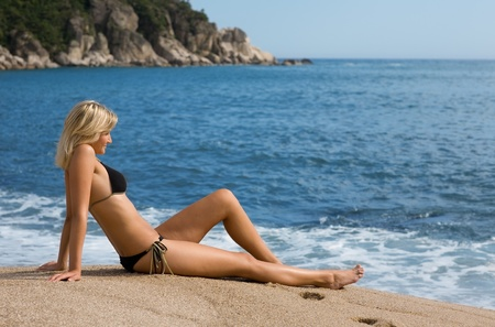 Attractive girl sitting on the sand beside the sea. Sunny day. Stock Photo - 9749542
