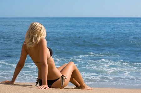 Sexy girl in bikini on a sandy beach. photo