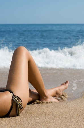 shapely legs: Lower half of the girl body lying on the beach by the sea. Stock Photo