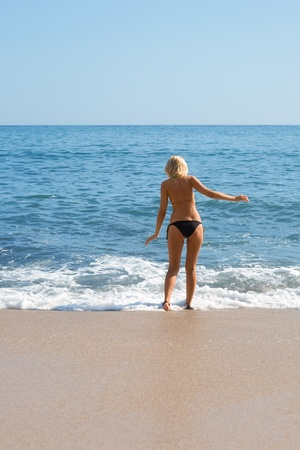 Attractive girl on the sandy beach by the sea. photo
