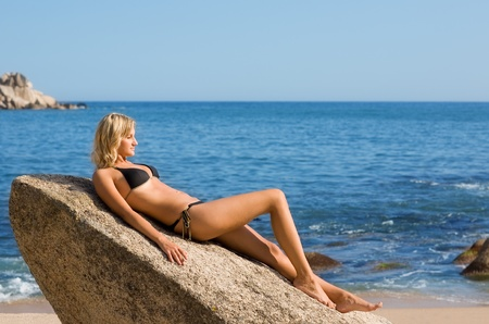 Beautiful girl lying on a rock by the sea. Stock Photo - 9749549