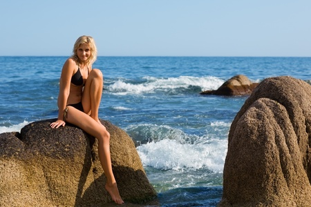 Attractive girl is sitting on a rock by the sea. Stock Photo - 9749573
