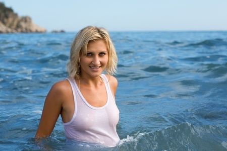 Beautiful young sexy woman swims in the sea photo