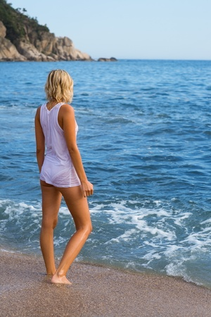 Young woman standing on the beach. photo