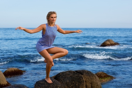 Young woman does yoga exercises by sea. photo