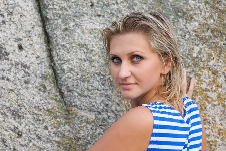 Girl with blue eyes in the striped shirt on the background of rocks. photo