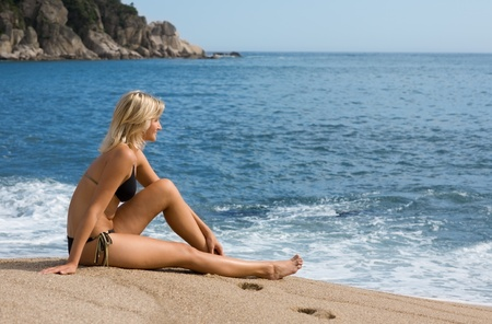 Attractive girl sitting on the sand beside the sea. Sunny day. photo